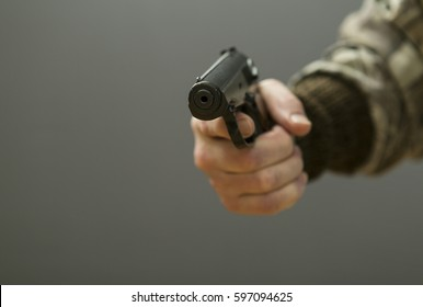 Makarov pistol in the man's hand on a dedicated background.