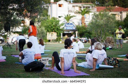 MAKARSKA,CROATIA - 21 JUNE,2017: People gathered to celebrate International Yoga Day on Croatian Coast.Group yoga lovers course.Women do the work out outdoor in green park