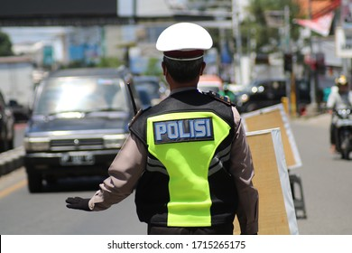 MAKASSAR, INDONESIA - APRIL 27 2020: Traffic police officers regulate the flow of traffic at the Makassar City border