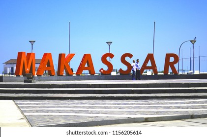 MAKASSAR, INDONESIA - AUGUST 14 2018: A number of tourists are standing at the Losari Beach Pavilion, right in the building that reads the word Makassar. This location is on the outskirts of Makassar