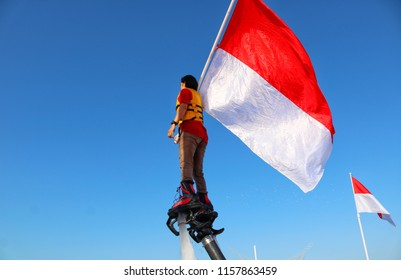 MAKASSAR, INDONESIA - AUGUST 17 2018: A female officer uses a flying board holding an Indonesian flag to fly at the celebration of Indonesia's independence proclamation in Losari beach, Makassar