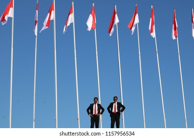 MAKASSAR, INDONESIA - AUGUST 17 2018: Two men were standing under a number of Indonesian flags that were hoisted neatly at Losari Beach Pavilion, Makassar