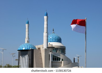 MAKASSAR, INDONESIA - AUGUST 17 2018: Amirul Mukminin Mosque, known as the floating mosque at the Losari Beach Pavilion in Makassar with a red and white flag in front of it