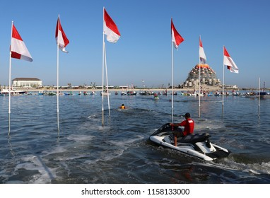 MAKASSAR, INDONESIA - AUGUST 17 2018: A man is practicing jet skiing in Losari waters around a flagpole lined up neatly on Losari Beach, Makassar