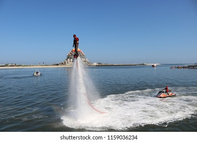 MAKASSAR, INDONESIA - AUGUST 17 2018: A man is riding a flying board on the water. This activity was carried out as an exercise for raising the Indonesian flag above Losari Beach in Makassar