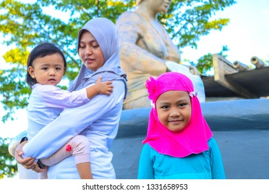MAKASSAR, INDONESIA - MARCH 5 2019: A mother and two daughters were at the tourist site of Losari Beach, Makassar