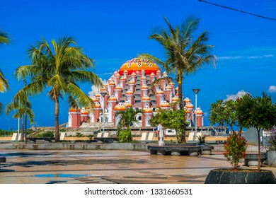 MAKASSAR, INDONESIA - MARCH 5 2019: Losari beach atmosphere with a background of a 99-dome mosque in Makassar. This place is always visited by residents to enjoy the sunset
