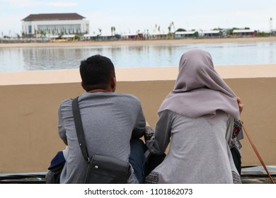 MAKASSAR, INDONESIA - MAY 24 2018: A young couple was sitting backward looking at Losari beach. Both are enjoying the panorama on the beach in Makassar