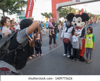 Makassar, Indonesia - November 1, 2015: A family posed with a man wears Disney's Mickey Mouse costume during car free day event at Losari Beach.