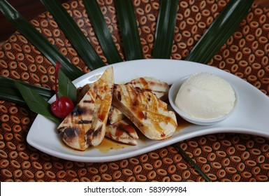 Makassar Indonesia traditional dessert named Pisang Epe, Grilled banana in  durian and brown sugar caramel with ice cream