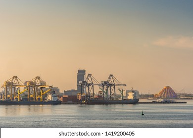 Makassar, Sulawesi, Indonesia - February 28, 2019: Early morning light over ships and container terminal with orange new Masjid Raya Sulawesi Selatan mosque in back.