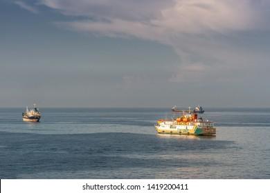 Makassar, Sulawesi, Indonesia - February 28, 2019: Yellow and white Passenger and cargo ship Sabuk Nusantara leaves the harbor on a flat blue sea under a light blue sky.
