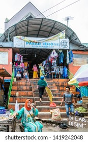Makassar, Sulawesi, Indonesia - February 28, 2019: Terong Street Market. Entrance to the covered part of the street market featuring clothes and non-fresh items. People waving and smiling as the camer