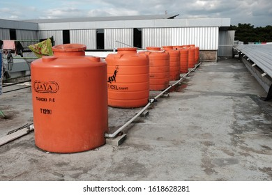 Makassar, Sulawesi Selatan / Indonesia - September 3 2019: A row of orange water tank or reservoir on a rooftop of a refugee Shelter.