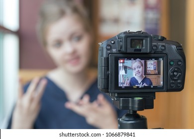 Makati, Philippines - April 8, 2018: Camera recording a young caucasian female blogger gesturing while making a video, selective focus on camera