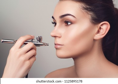 Make up with airbrush. Girl face with perfect skin. Fashion model with nude make up. Makeup lips. Sensual girl. Makeup artist using airbrusher. Isolated on grey.