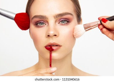 Make up Applying. Beuatiful model face with Cosmetic Powder Brushes for Make up. Perfect Skin. Red Lipstick brush .  Makeover