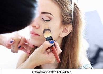 make up artist apply base foundation on the model face