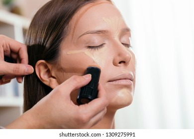 Make up artist applying face powder and corrector foundation to a female client's face, contouring the face
