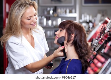 Make up artist applying face powder with a brush in a beauty store. Selective focus.