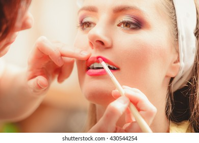 Make up artist applying lipstick with brush on pretty gorgeous woman lips. Closeup of visagiste and young girl. Beauty and makeup concept.