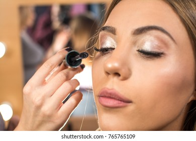 Make up artist applying mascara to fashion model.
