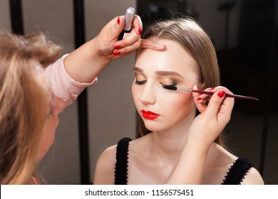 make up artist carefully applying a mascara on lashes of a beautiful model with flawless makeup in a beauty studio