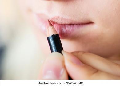 make up artist colors lip contour using a stick