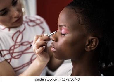 Make up artist doing makeup for african fashion model in studio