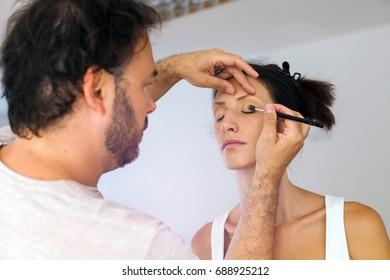Make up artist doing makeup for model