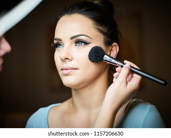 Make up artist doing professional make up of young woman.