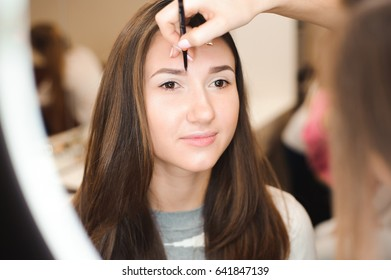 Make up artist doing professional make up of young woman. Beauty shcool.