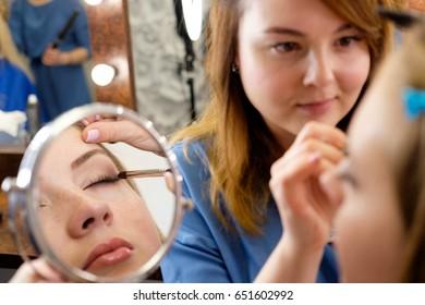 make up artist making makeup, mirror reflection