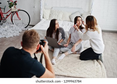 Make up artist prepare two twins models with laptop on studio before photoshoot. Photographer shooting. Teamwork together.