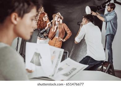 Make up artist preparing attractive model before photoshoot