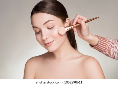 Make up artist preparing beautiful brunette caucasian young woman, applying powder on her cheeks with a brush. Clean, fresh, natural, flawless skin. Soft smile on her face. Close up