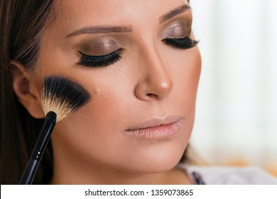 Make up artist working in a make up studio, applying the highlighters to female client's face