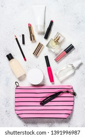 Make up bag with cosmetic beauty products spilling out on white background. Flat lay image with space for text.