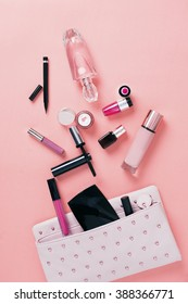 Make up bag with cosmetics on pink background