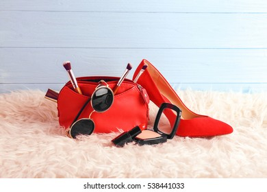 Make up bag with cosmetics and red heels on blue wooden background