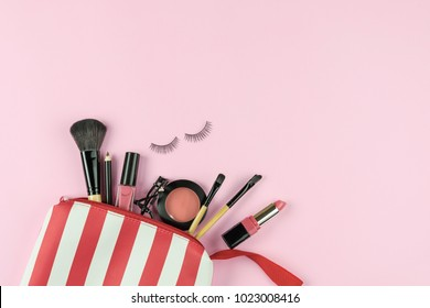 Make up bag with various cosmetics and brushes isolated on pink background, Top view, Beauty concept
