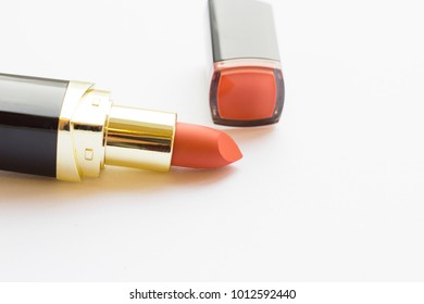 Make Up Beauty Concept. Matte coral lipstick in black tube on white background, close up