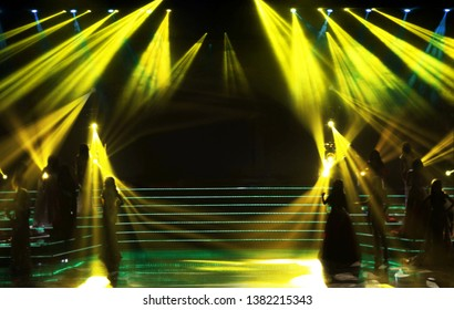Make it Blur out focus Group silhouette of Miss Beauty Pageant Contest stand on left right side of world class stage with yellow lighting beam shine to contestances, low exposure, copyspace empty area