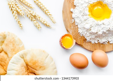 Make bread concept. Flat bread near wheat ears, flour and eggs on white background top view
