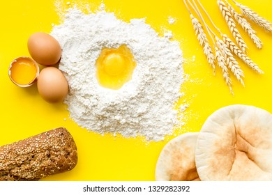 Make bread concept. Bread near wheat ears, flour and eggs on yellow background top view