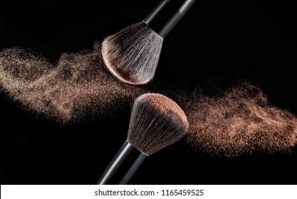 Make up brush with gold powder splashes on black background. pink powder explosion