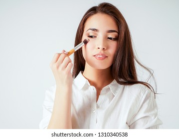 Make up brush in hand of smiling asian young woman with dark long hair on white background