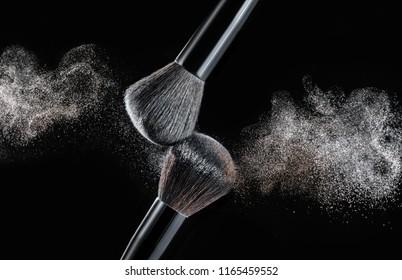 Make up brush with white and gold powder splashes on black background. white powder explosion
