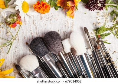Make up brushes on wooden background next to wild flowers. Professional cosmetics