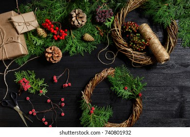 Make a Christmas wreath with your own hands. Spruce branch, Christmas wreath and gifts on a black wooden background